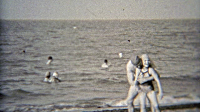 1937: Dad playing with daughter at the beach with swim caps on. video