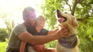Dad plays with his cute son and their dog outside video