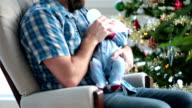 Dad rocking his newborn close to Christmas tree and Snowstorm video