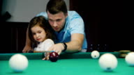 Dad teaches his daughter to play billiards. It shows how to hold the cue video