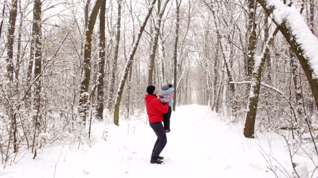 Dad throws up his daughter to the sky in winter. video