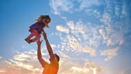SLO MO TU Dad tossing her daughter into the air at sunset video