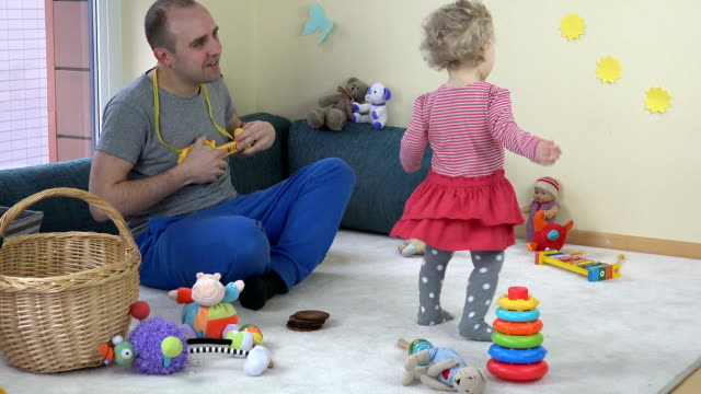 Daddy play with toy guitar and loved toddler girl dance at home. video