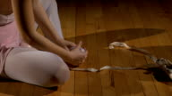 Dancer takes off ballet shoes and rubs her feet video