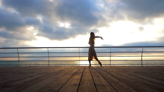 Dancing ballerina in beige silk dress and pointe on embankment above ocean or sea beach at sunrise or sunset. Silhouette of young beautiful blonde woman with long hair practicing stretching and classic exercises with emotions. SLOW MOTION video