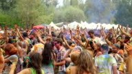 Dancing crowd covered in colorful paint, people enjoying fest video