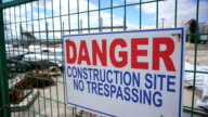 Danger construction site no tresspassing sign panning shot video
