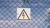 Danger sign of high voltage damage. Electricity of the net. Substation behind the fence. Warning sign of danger. high voltage. Electric wires with supports video