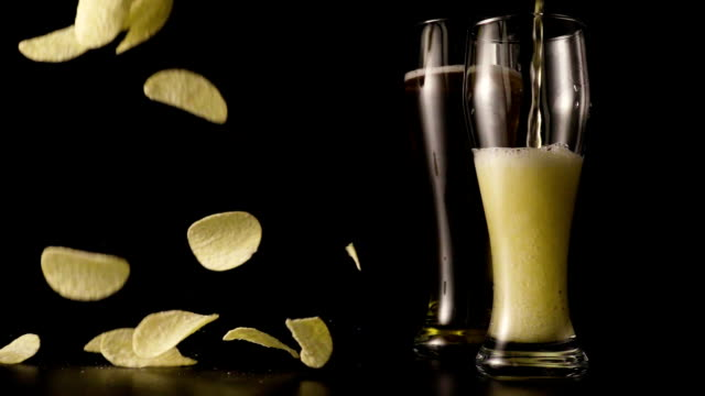 Dark beer is poured into a glass of potato chips falling in slow mo video