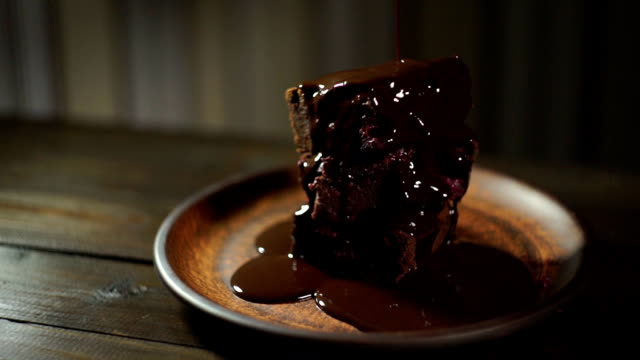 Dark chocolate flowing on brownie cake. Chocolate dripping on delicious dessert video