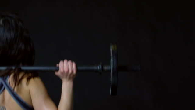 Dark haired woman doing barbell squats, back view, shot on R3D video