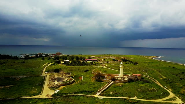 Dark stormy sky before the rain. Summer landscape on the island of Cyprus. The sea and the coast. Drone Point of View. Ancient lighthouse near Mediterranean Sea . video