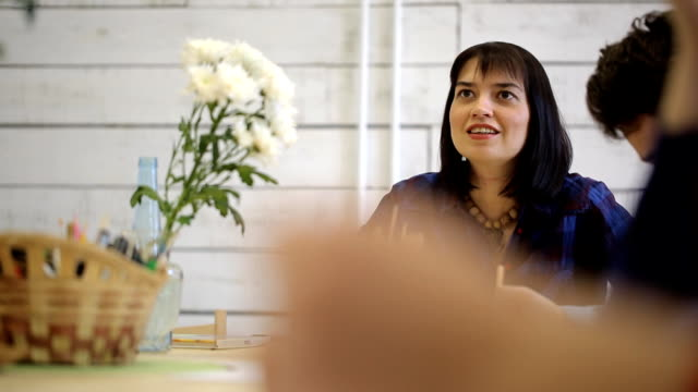 Dark-haired and black-eyed woman sits at table, holds pencil and talks video