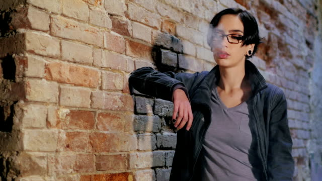 Dark-haired young woman smoking electronic cigarette on brick wall background video