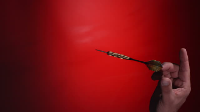 Dart hits bulls-eye on dartboard, slow motion video