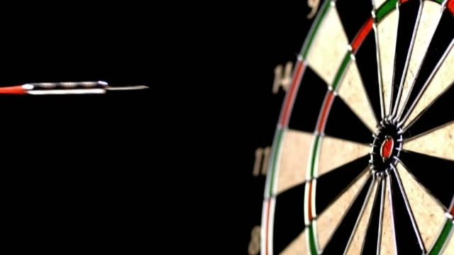 Dart hitting bull's eye, slow motion video
