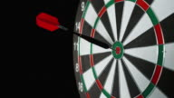SLO MO dart with red flight hitting the bulls eye video