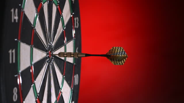 Darts hitting dartboard, multiple shots, slow motion video