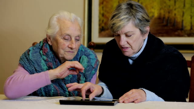 daughter adn her mother are using tablet: internet, old, ancient, technology video