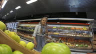 POV Daughter and father choosing green apples in supermarket video