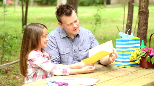 Daughter gives dad handmade Father's Day card. Outdoors. Child, parent. video