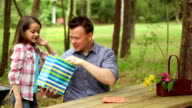 Daughter gives daddy Father's Day gift. Outdoors. Child, parent. video