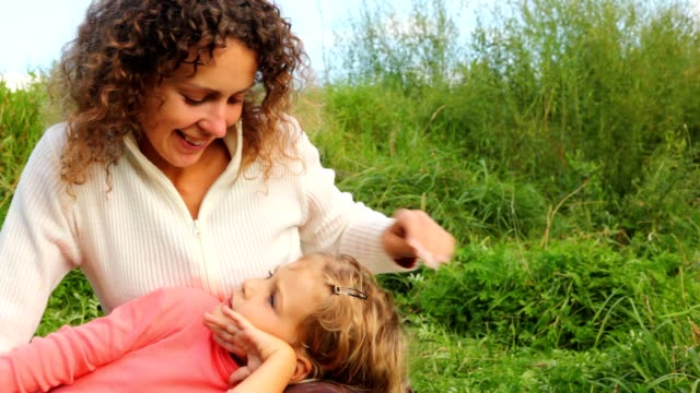 Daughter lies beside mom knee on green field video