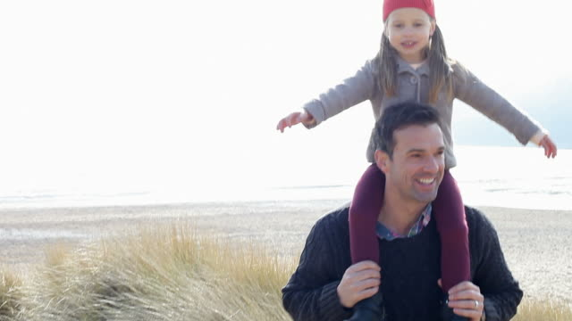 Daughter Riding On Father's Shoulders Walking Through Dunes video