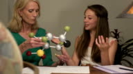 Daughter Shows Mother her Science Project of a Molecule CU video
