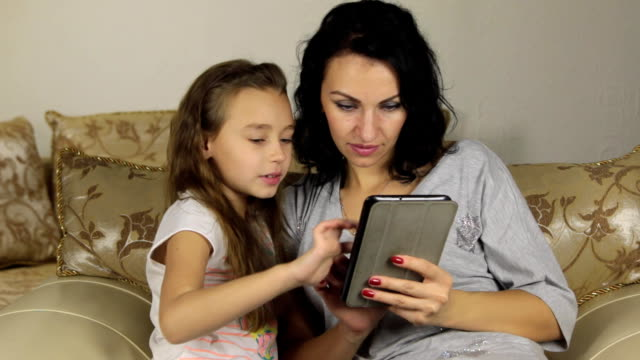 Daughter teaches mother to play the game on the tablet video