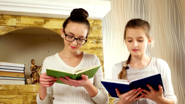 daughters doing homework near fireplace, girls reading books, children spend free time together video