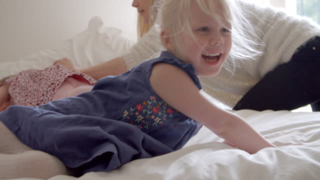 Daughters Having Fun Jumping On Parents Bed In Slow Motion video