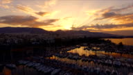 Dawn in the Greek marina, Athens. Aero video shooting. A lot of different yachts, catamarans moored to piers. In the background is the landscape of the mountains and the city houses. Summer clear morning, calm Mediterranean sea video
