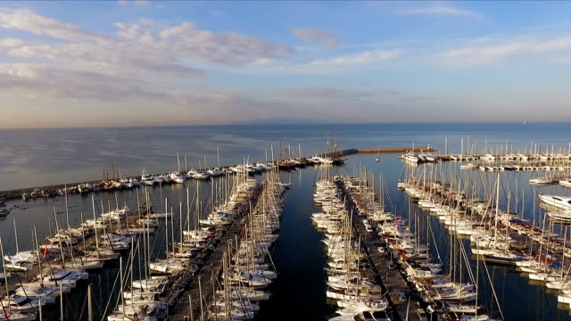 Dawn in the Greek marina, Athens. Aero video shooting. A lot of different yachts, catamarans moored to piers. In the background is the landscape of sea , blue sky. Summer clear morning, calm Mediterranean sea video