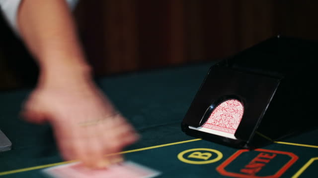 Dealer in casino deals the cards by the card feeder video
