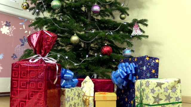 Decorated christmas fir tree and colorful gifts presents boxes video