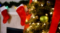 Decorated Christmas tree standing next to stockings hanging above fireplace video