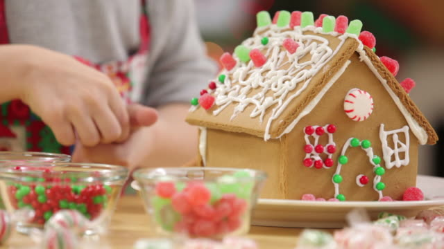 Decorating a gingerbread house for Christmas video