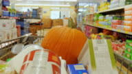 Decorating for Halloween. Big pumpkin lays in a basket with purchases. Trolley rides through the store video