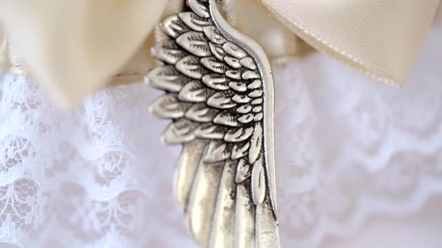 Decorative metal element is sewn to light pink silk ribbon video