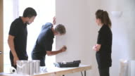 Decorator instructing young colleagues painting a room video