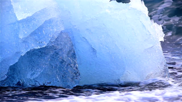 Deep blue glacial ice, splashed by ocean waves on shore, Jokulsarlon, Iceland video