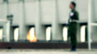 Defocused eternal flame memorial and armed guard. FullHD bokeh background video video