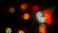 Defocused lights behind raindrops video