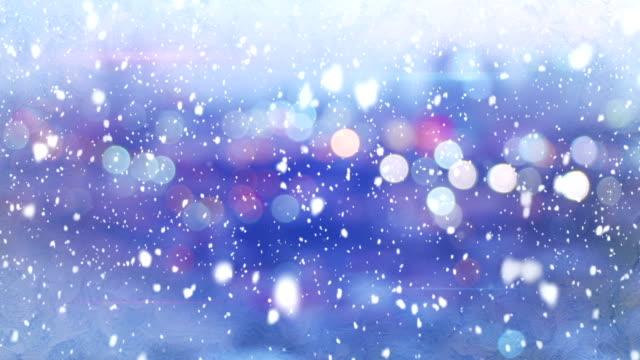 defocused lights evening wintry city and snowfall loop video