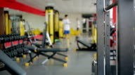 Defocused people using sports equipment for exercising in gym at video
