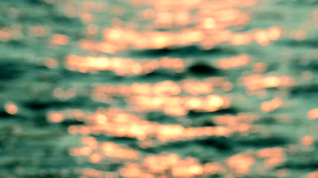 Defocused shot of a wavy water surface with a beautiful bokeh of sun glares which are reflected from the surface of water video