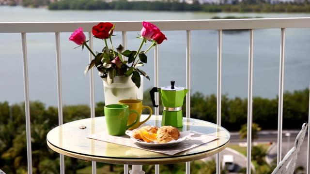 Delicious breakfast  with coffee fresh croissants and slice of orange fruit on  balcony video