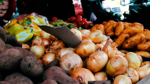 Delicious fresh onion peppers and other vegetables with price tags are on market counter video