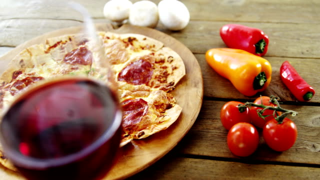Delicious pizza with a glass of wine, vegetable and spices video
